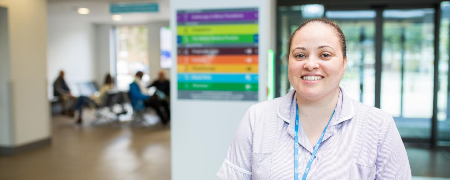 A nurse smiling at the camera in a hospital