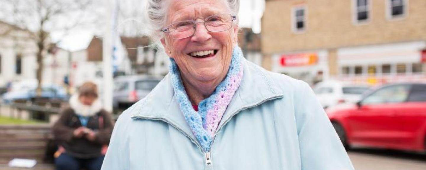 Elderly woman smiling face on to the camera