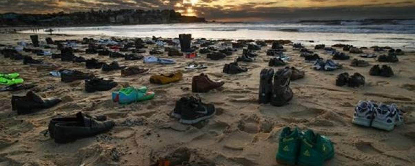 94 pairs of empty shoes on a beach