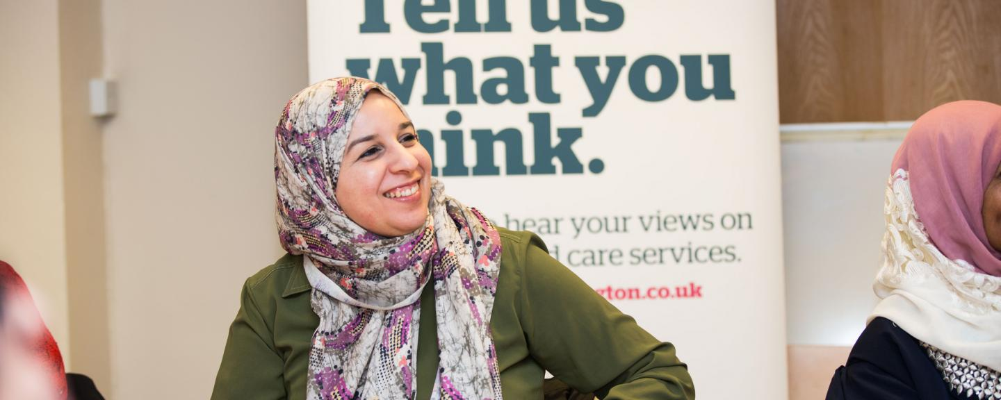 Woman in headscarf infront of a Healthwatch banner that says 'Tell us what you think'