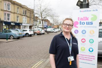 Healthwatch Staff member infront of some branded  promotional material at a Healthwatch event