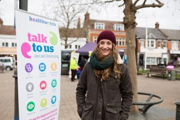 Student volunteer standing infront of a Healthwatch banner