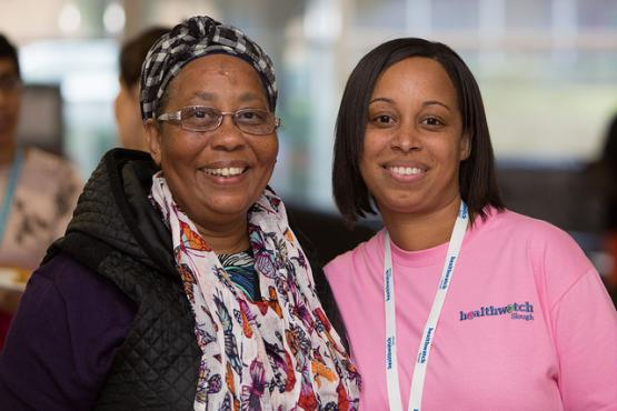 Two people wearing Healthwatch branded materials