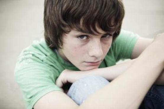 Boy sitting hugging knees